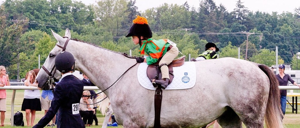 Small child riding a Thoroughbred horse