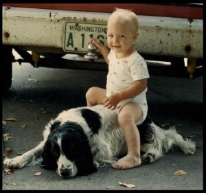 Baby sitting on a black and white dog