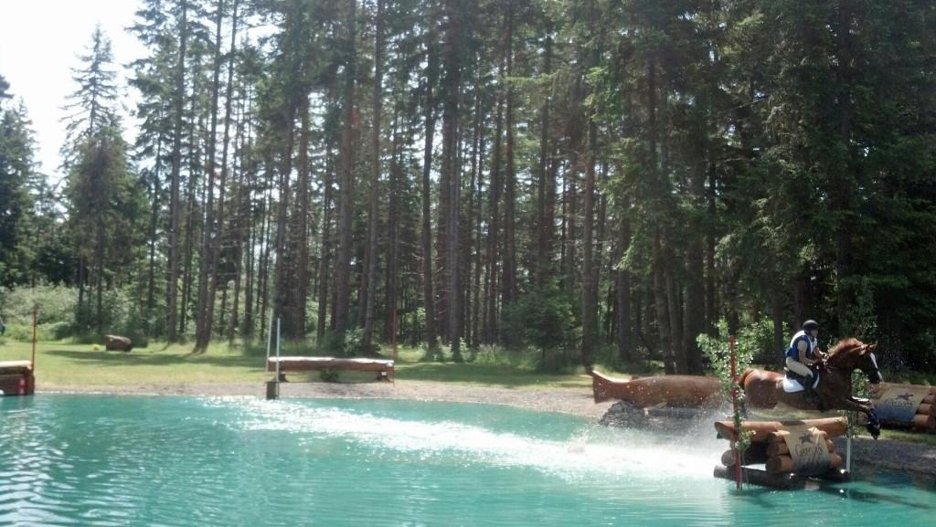 Horse galloping through the water jump at Aspen Farms Horse Trials